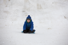 This image shows a boy sledding.