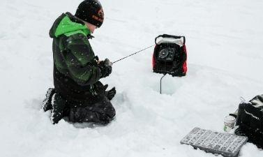 This image shows a picture of a child fishing at the Youth Ice Fishing Derby.