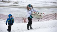This image shows two kids walking up the hill at the 2017 Cardboard Sled Race