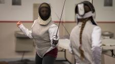 This image shows two girls in a fencing duel at the youth fencing program.