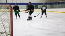 This image shows men skating on the ice at Drop In Hockey.