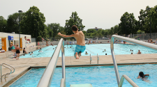 This image shows a boy diving into Island Park Pool.