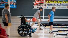 This image shows three kids bowling during the youth adaptive summer camp.