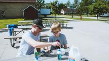 This image shows a boy and instructor making a craft during the youth adaptive summer camp.