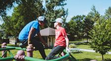 This image shows two boys on the playground during the youth adaptive summer camp.