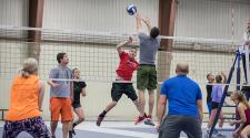 This image shows adults playing a coed volleyball game.