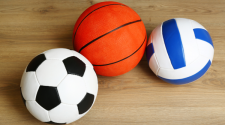 This image shows a soccer ball, basketball and volleyball sitting on the court.