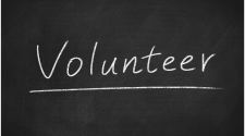 This image shows the word volunteer written on a white board.