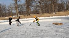 This image shows a player trying to score while another player tries defending at the Fargo Pond Hockey Classic.