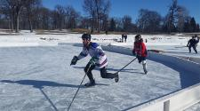 This image shows two players skating at the Fargo Pond Hockey Classic.
