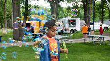 This image shows a boy playing with the bubbles during Gathering on Tuesday's.