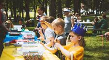 This image shows some kids making crafts at a table during Midwest Kids Fest.