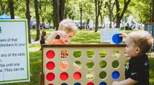 This image shows two boys playing giant, yard sized checkers at Midwest Kids Fest.