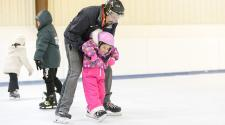 This image shows a father and daughter ice skating.
