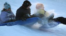 This image shows three children sledding down the hill together.
