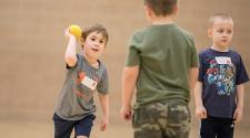 This image shows two boys playing catch at sports sampler.
