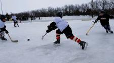 This image shows two players chasing the puck at youth pond hockey.